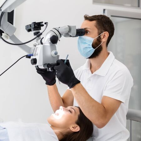 Highly qualified bearded male dentist using modern technologies in dental treatment, complicated cases in stomatology Stockfoto
