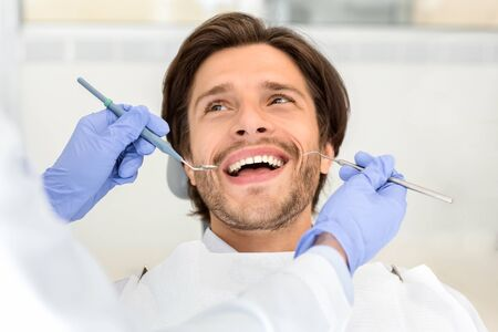 Portrait of handsome cheerful man attending dentist, looking at doctor with smile on his face