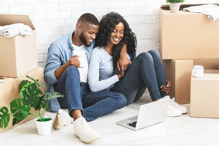 Relocation and moving concept. Cheerful african couple sitting on floor at new apartment, watching movie online on laptop, having break, empty space