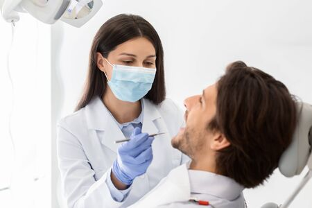 Close up of man having check up in new dental office, female doctor in medical mask assisting, copy space