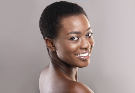 Beauty portrait. Beautiful black woman with short hair, white smile and clean glowing skin over grey studio background
