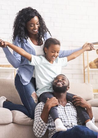 Happy family lifestyle concept. Afro mother, father and their little daughter having fun at home together. Stock Photo