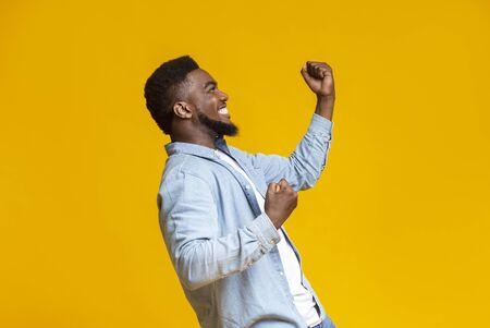 Sì l'ho fatto. Ritratto di profilo di un uomo afro eccitato che celebra il successo con i pugni chiusi, sfondo giallo con spazio libero