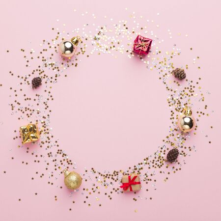 Cute Christmas round frame of balls, presents and cones on pink background, copy space for text