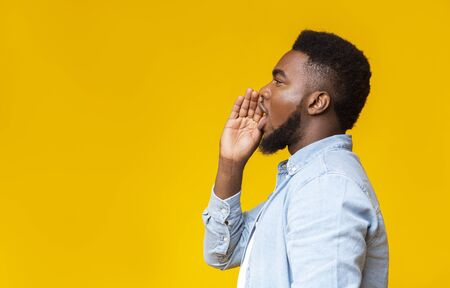 Profile portrait of black guy making announcement, shouting at copy space on yellow studio background, sharing news.