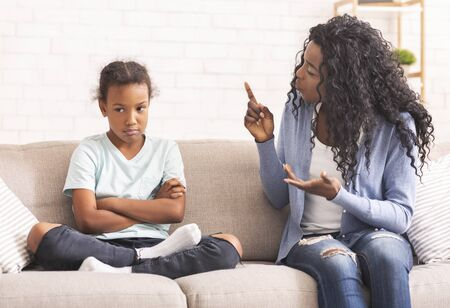 Angry african american mother scolding naughty little daughter, sitting on couch at home Imagens