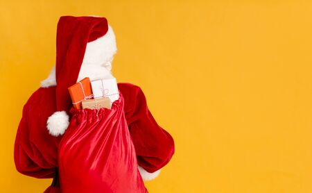Merry Christmas. Santa holding big sack with presents on orange background, view from the back, copy space