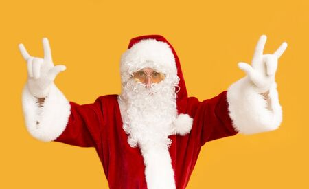 Cristmas rock festival. Young Santa in sun glasses showing horn sign on orange background Stock Photo