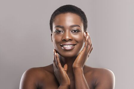 Beautiful black woman with short hair touching her smooth cheeks, applying cream or lotion on face and looking at camera, copy space