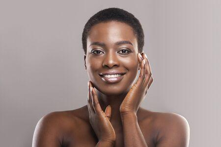 Hermosa mujer negra con cabello corto tocando sus suaves mejillas, aplicando crema o loción en la cara y mirando a cámara, espacio de copia