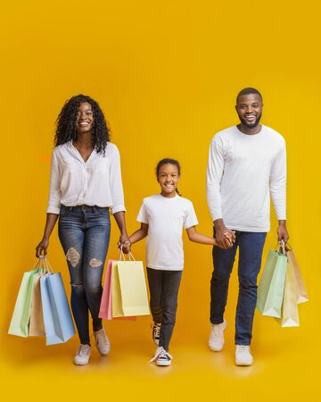 Shopping Weekend. Happy African American family of three walking with shopper bags in studio, yellow background with copy space