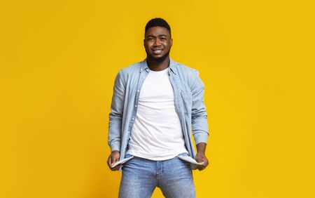 Im broke. Desperate black man showing empty turned out pockets over yellow studio background Stock Photo