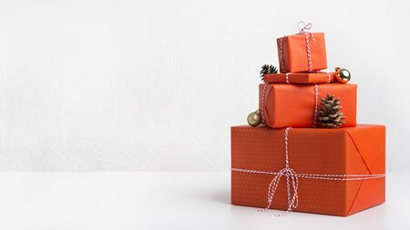 Creative Christmas presents wrapping in red paper on white background, panorama, copy space