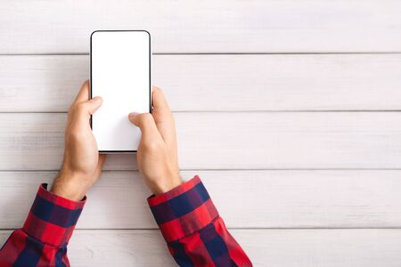 Mans hands messaging on smartphone with blank screen over white wooden background, free space Stock fotó