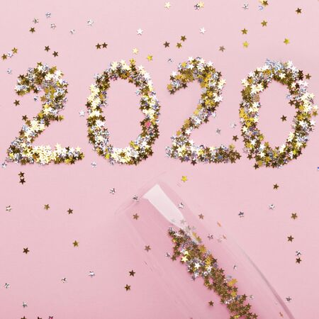 Celebration concept. Big 2020 letters and champagne on pink background