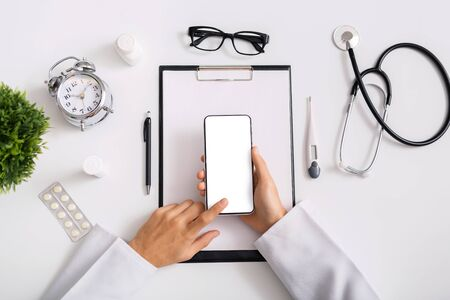 Modern technologies in healthcare sector. Male doctor using smartphone with blank screen at workplace, top view
