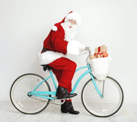Eco friendly Christmas. Santa Claus riding a retro bicycle full of Christmas gifts on white background Stock fotó
