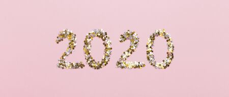 Happy new Year. 2020 big letters of gold confetti on pink background, panorama