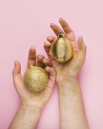 Close up of woman hands with gold balls on pink background, Christmas creative greeting card