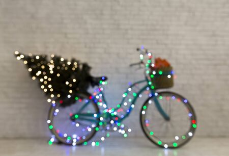 Creative Christmas blue bicycle with pine tree and gifts wrapping in lights, copy space, blurred background