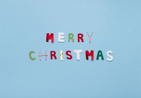 Merry Christmas text of colored letters on blue background, copy space