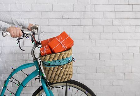 Unrecognizable woman riding a bicycle with Christmas presents on white bricks wall background, copy space