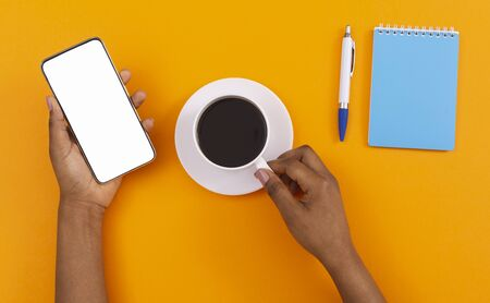 Good start of the day. African american woman holding smart phone with blank screen and drinking morning coffee over orange background, top view Zdjęcie Seryjne