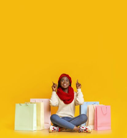 Big deal. Amazed black winter girl with shopping bags sitting on floor and pointing up at empty space, yellow studio background