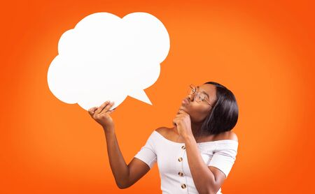 Hm, Great Idea. Young Black Woman Holding Speech Bubble Thinking About Something Standing Over Orange Studio Background. Mockup Banco de Imagens