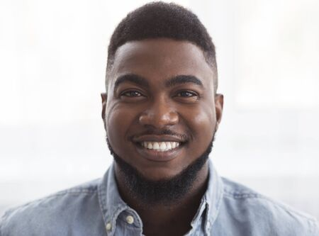 Closeup portrait of young attractive black guy with happy face expression, copy space