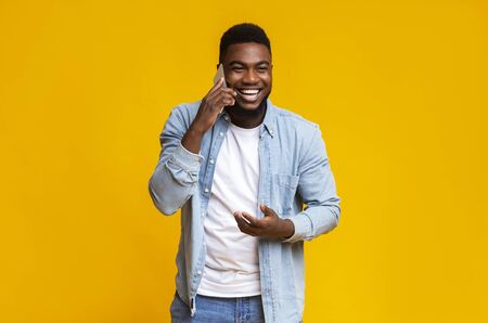 Cheerful african american man talking on phone and laughing out loud over yellow studio background, free space