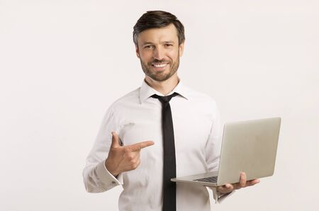 Cheerful Man Holding Laptop Computer Pointing Finger At It Standing Over White Background. Studio Shot