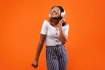 Music App. Cheerful Black Girl In Headphones Listening To Favourite Song And Dancing Over Orange Studio Background.