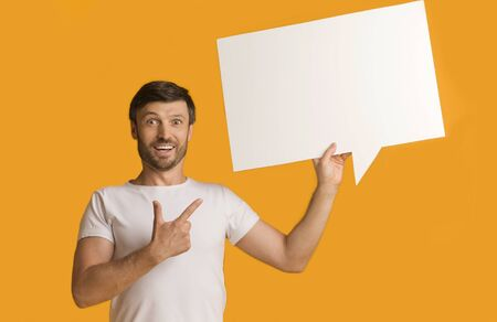 Look Here. Shocked Guy Showing Blank Speech Bubble Pointing Finger Standing Over Yellow Background In Studio.