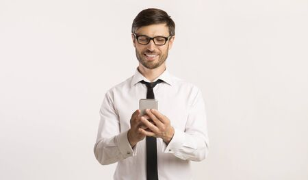 Businessman Using Mobile Phone Texting In Corporate Chat Standing Over White Studio Background. Free Space Imagens