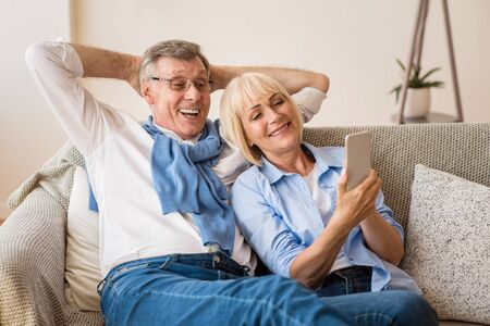 Happy mature couple using cellphone, surfing internet online, sitting on sofa at home, free space