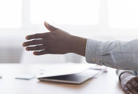 Hand of black hr manager extended for handshake after successful job interview, free space Banco de Imagens