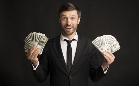 Wealth. Excited Businessman Holding Money Cash Standing Over Black Background. Studio Shot