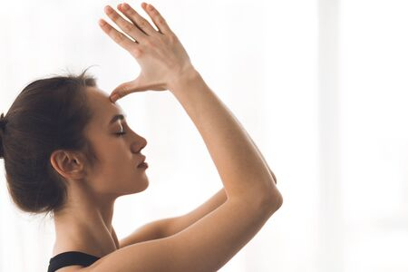 Yogi woman doing namaste gesture, hands to forehead in light studio, free space, side view