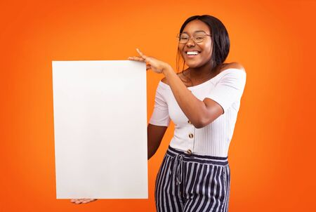 Great Offer. African American Girl Holding Blank Board For Text Standing On Orange Background In Studio. Mockup Imagens
