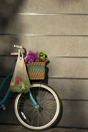 Creative card with eco concept. Retro bicycle with wild flowers and eco shopping bag over gray wall, sun lights, vertical panorama, copy space
