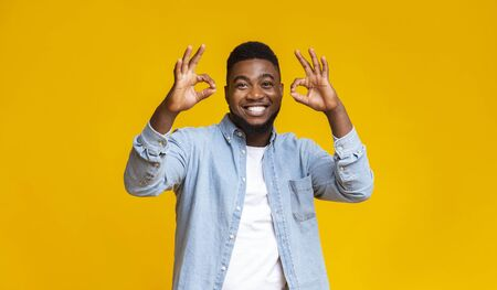 Everything is OK. Joyful african american man showing okay gesture with two hands over yellow studio background, free space