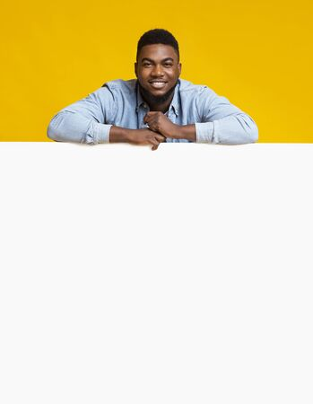 Free Space For Your Ad. Positive african american guy leaning on white board for advertisement, yellow background.