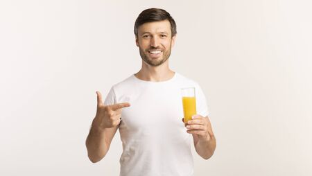 Middle Aged Man Holding Orange Juice Pointing Finger At It Standing Over White Studio Background. Panorama, Free Space
