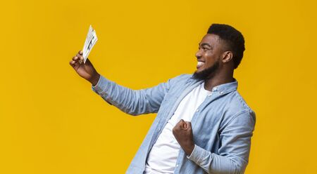 Overjoyed african american guy celebrating success with dollar bills in hand, standing over yellow studio background, panorama Stock Photo