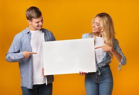 Happy young guy and girl holding blank advertising board and pointing on it against yellow background, free space