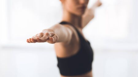 Woman exercising yoga in warrior pose, focus on hand. Girl practicing yoga in studio, panorama Stock Photo