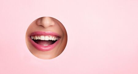 Perfect smile. Woman smiling through hole in pink paper, copy space, panorama Imagens