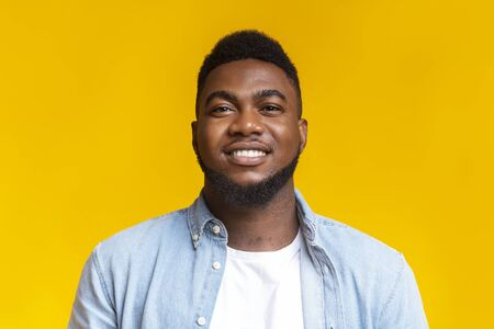 Be yourself. Closeup portrait of confident black millennial guy over yellow background, copy space Stock Photo