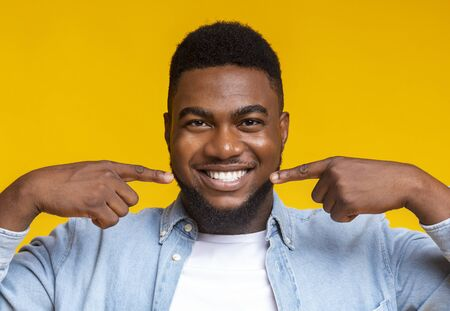 Dental health. Closeup of handsome black guy smiling wide and pointing at his perfect teeth, yellow background with copy space